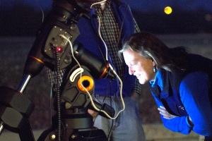 Darlene Sims examines Curt Hughes' telescope